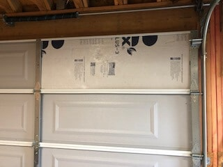 foam insulation board installed in garage door panel.