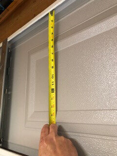 Measure the garage door panel including the space behind the lip.
